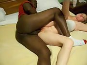 Black on white couple having missionary sex in couch